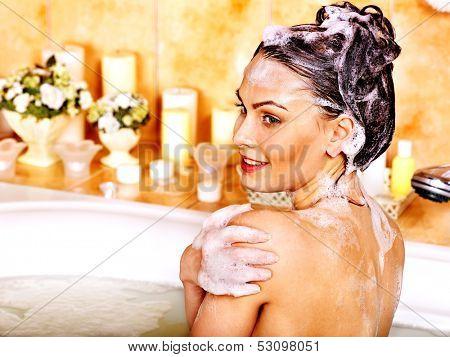 Yong woman washing hair in bubble bath.