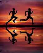 Silhouettes of two runners on sunset fiery background. Water reflection. Element of design. poster