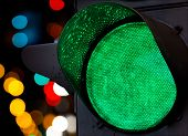 Green traffic light with colorful unfocused lights on a background poster