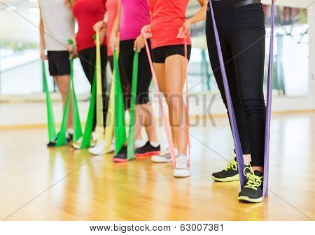 fitness, sport, training, gym and lifestyle concept - group of people with working out with rubber bands in the gym