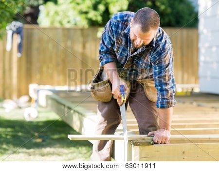 Mid adult worker sawing wood at construction site