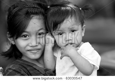 EL NIDO, PHILIPPINES, JANUARY 11 : Poor filipino little girl holding her younger sister, El Nido, Philippines, on january 11, 2014