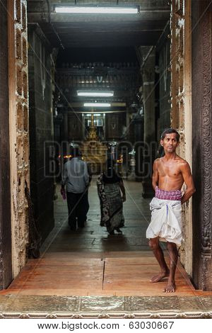 TIRUCHIRAPALLI, INDIA - FEBRUARY 14, 2013: Unidentified Indian brahmin (traditional Hindu society) priest standing in gateway of Sri Ranganathaswamy Temple