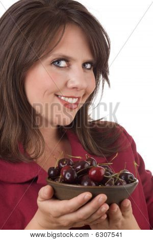 Young woman holds a bowl of cherries; isolated on white