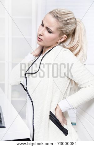 Young beautiful business woman has pains on her back - disc herniation - lack of exercise or not ergonomic working place.