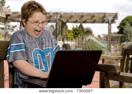 Smiling Boy Using A Computer