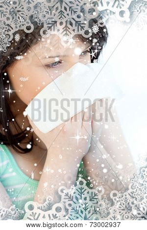 Portrait of a sick brunette teen girl blowing against snow falling
