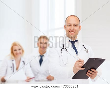 medicine, profession, teamwork and healthcare concept - smiling male doctor with clipboard and stethoscope writing prescription over group of medics