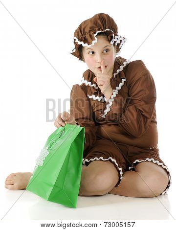 A barefoot elementary gingerbread girl gesturing shh! while preparing to peek into a green gift bag.  On a white background. poster