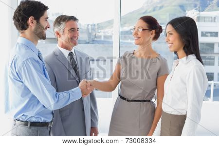 Two fellow employees shaking hands with other workers