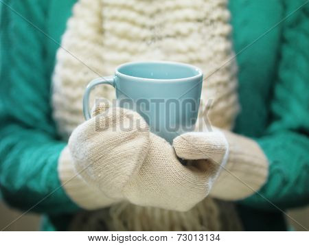 Female hands holding hot mug close up. Woman hands in white woolen mittens holding a cozy cup with hot cocoa, tea or coffee. Winter and Christmas time concept.