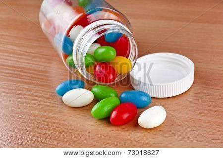 Colored Pills  JellyBeans pouring out of the plastic bottle on surface wooden table