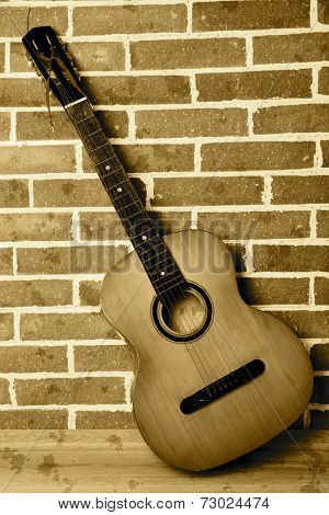 Guitar on floor on bricks wall background