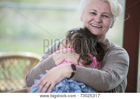 Portrait of happy grandmother hugging granddaughter in house