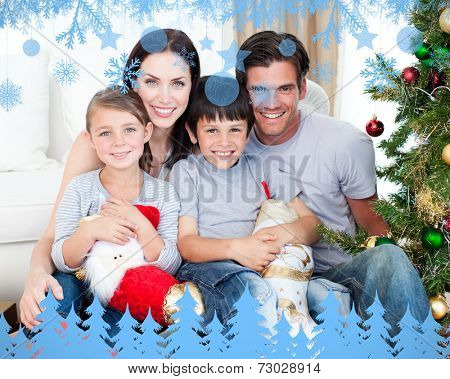 Portrait of a smiling family at Christmas time holding lots of presents against snow flake frame in blue