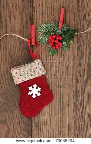 Christmas stocking decoration with holly and fir hanging on a string line over oak background. poster
