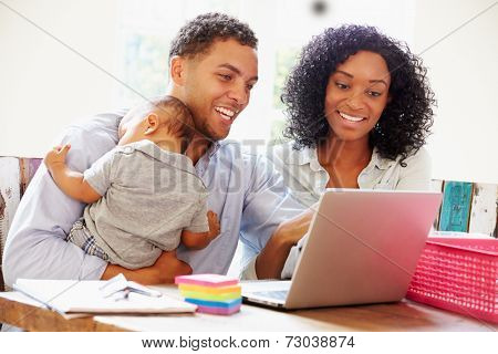 Parents With Baby Working In Office At Home