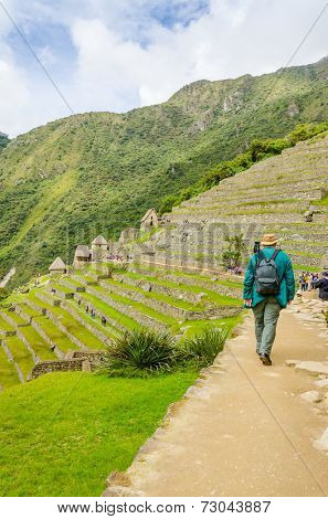 MACHU PICCHU, PERU - MAY 3, 2014 - crowds of tourist explore ruins of old city early in the morning while senior tourist walks with a backpack