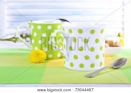 Two polka dot cups with sugar and wildflowers on table on light background poster