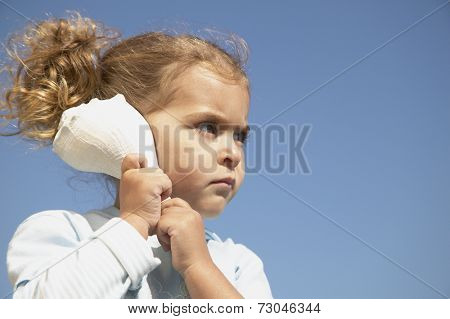 Young girl listening to echo in seashell