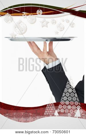 Welldressed man holding silver tray against christmas frame