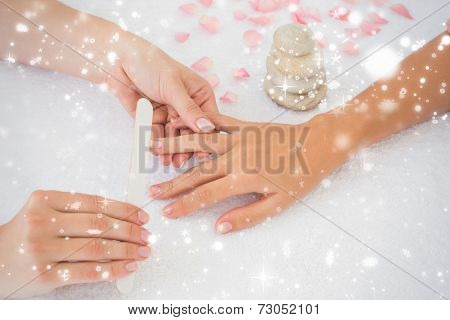 Nail technician filing customers nails against snow falling