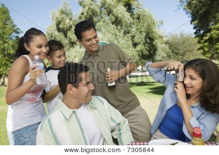 Woman using digital camera photographing son (13-15) with father brother and sister.