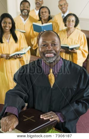 Minister at altar with Bible gospel choir in background portrait