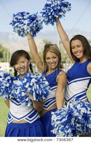 Cheerleaders waving blue and white pom-poms (portrait)