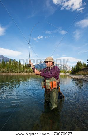 fisherman casting a fly in a mountain river.