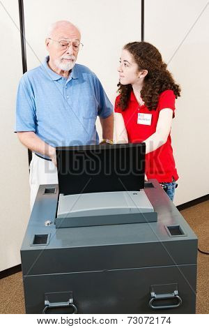 Young polling place volunteer helps a senior voter cast his ballot on new electronic equipment.
