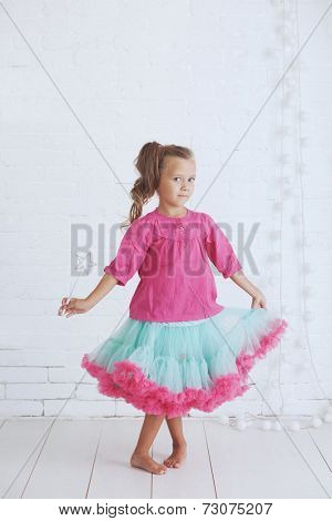 Studio portrait of cute little princess girl wearing holdiday candy tutu skirt holding magic wand