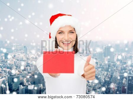 christmas, holdays, people, advertisement and sale concept - happy woman in santa helper hat with blank red card showing thumbs up gesture over snowy city background