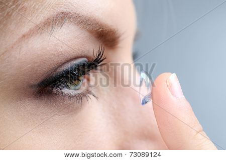 Medicine and vision concept - young woman with contact lens, close up poster