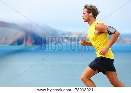 Athlete running man - male runner in San Francisco listening to music on smartphone. Sporty fit young man jogging by San Francisco Bay and Golden Gate Bridge. Jogger training with smart phone armband, poster