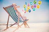 Woman in sunhat sitting on beach in deck chair using tablet pc with colourful computer applications poster
