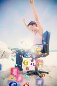 Cheering brunette using laptop on the beach sitting on swivel chair with colourful computer applications poster