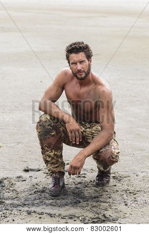 Kneeling Shirtless Soldier On The Beach Sand