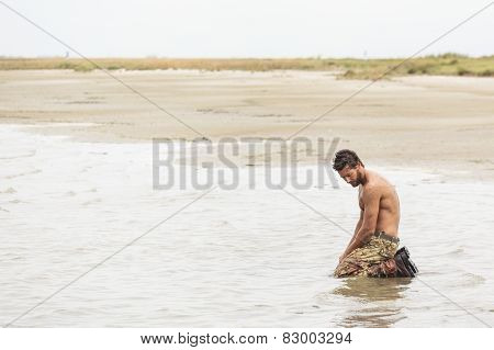 Kneeling Shirtless Soldier At The Sea Water