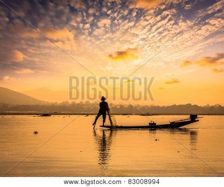 Myanmar travel attraction landmark - traditional Burmese fisherman sihouettes at Inle lake on sunset, Myanmar famous for their distinctive one legged rowing style