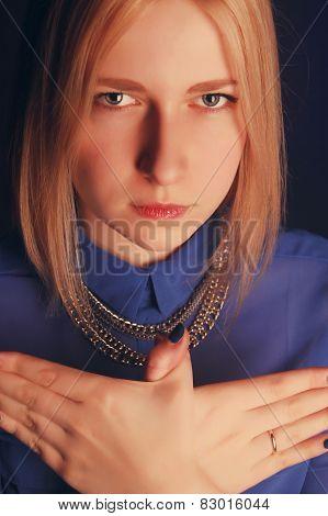 Girl In Blue Shirt Shows Bird With Hands. Studio Portrait.