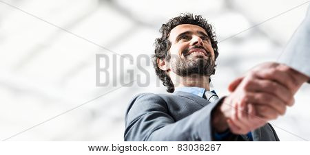 Business handshake. Businessman giving an handshake to close the deal. Lots of copyspace