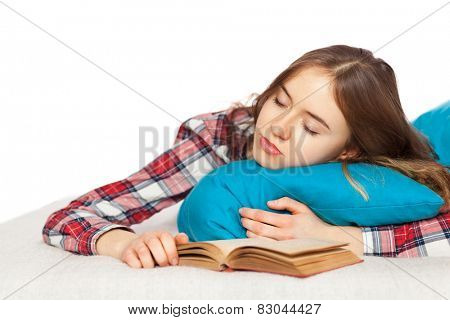 Young girl sleeping with a book in bed.