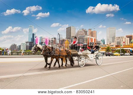 MELBOURNE, AUSTRALIA - JAN 15,2015: Coach with tourists crossing the bridge on Jan 15, 2015 in Melbourne, Australia. Horse carriage is a popular way for sightseeing in Melbourne.