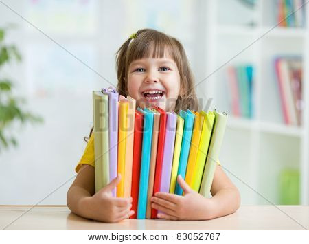 Cute kid girl preschooler with books indoor