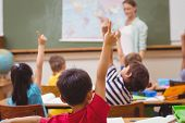 Pupils raising hand during geography lesson in classroom at the elementary school poster