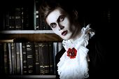 Handsome vampire nobleman studying ancient books in the library. Halloween. Dracula costume. poster