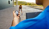 Closeup of man trainer hand using a chronometer to timing at tired athletic young woman in a hard training outdoors poster