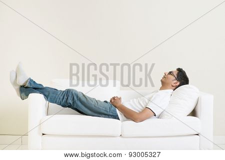 Indian guy daydreaming and rest at home. Asian man relaxed and sleep on sofa indoor. Handsome male model.