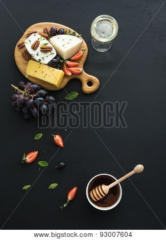 Cheese appetizer selection or whine snack set. Variety of cheese, grapes, pecan nuts, strawberry and